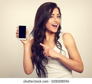 Happy smiling beautiful makeup woman holding and advertising mobile phone. Closeup portrait. Toned vintage portrait