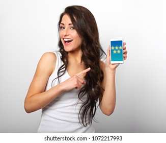 Happy smiling beautiful makeup woman holding and advertising mobile phone with advertising feedback from five stars on the screen on white background with empty copy space. Closeup portrait