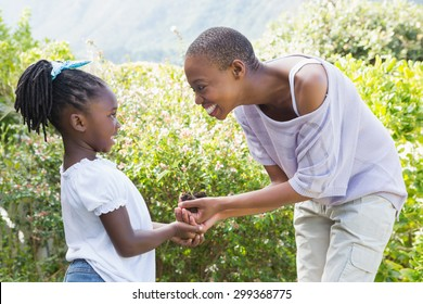 Happy smiling beautiful mother plant a flower with her daughter in a garden