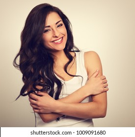 Happy smiling beautiful woman hugging herself with natural emotional enjoying face on white background. Love concept. Toned closeup portrait