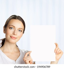 Happy smiling beautiful young business woman showing blank signboard, at office