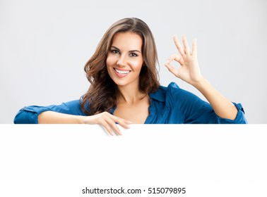 Happy smiling beautiful young business woman showing blank signboard with empty copyspace area for slogan or advertising text message, on grey background.