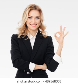 Happy smiling beautiful young businesswoman showing okay gesture, on grey background. Caucasian blond model in business presentation concept. Square composition.