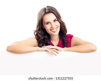 Happy smiling beautiful young woman in red smart casual clothing  showing blank signboard or copyspace for slogan or text, isolated against white background