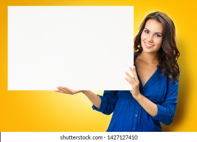 Happy smiling beautiful young woman showing blank sign board with copy space, isolated over yellow orange  background. Success in business concept. Brunette model in blue confident clothing at studio.