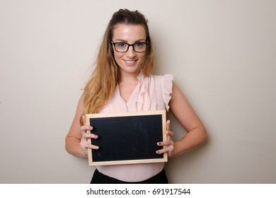 Happy smiling beautiful young woman showing blank signboard or copy space for slogan or text.