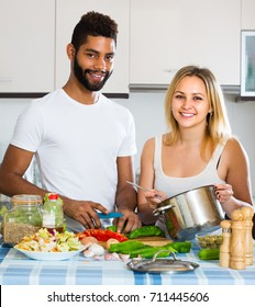 Happy smiling black guy and his young white wife preparing healthy dinner