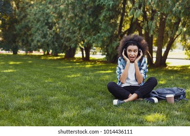 Happy smiling black woman sitting outdoors in city park. Casual student girl enjoying music in headset, sitting on green juicy grass. Leisure, recreation and urban lifestyle concept, copy space