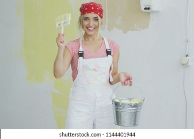 Happy smiling blond female in white overalls and red bandana holding paint bucket and brush in raised up hand standing at half-painted in pastel yellow color wall and looking at camera .