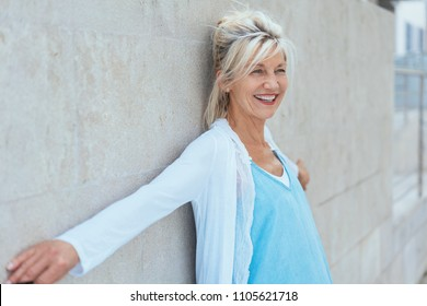 A happy, smiling, blond, mature woman leaning on a wall in happy lifestyle concept portrait.