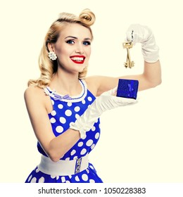 Happy smiling blond woman in pin-up style blue dress in polka dot, showing keys from new house or flat, over yellow background. Caucasian model in retro fashion, vintage and real estate concept.