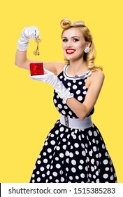 Happy smiling blond woman in pinup style black dress in polka dot, showing keys from new house, isolated over yellow color background. Caucasian girl posing in retro fashion, vintage and real estate.