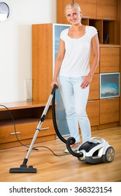 Happy smiling blonde girl in jeans vacuuming floor at home