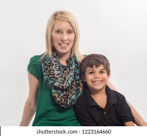 Happy, smiling blonde mother with dark haired, biracial son, sitting
