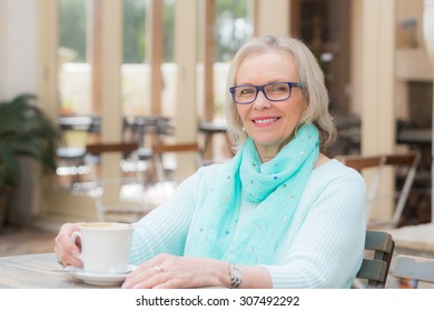 Happy and smiling blonde woman sitting at cafe with a coffee