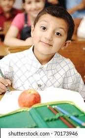 Happy smiling boy in classroom with an apple on the table