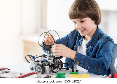 Happy smiling boy constructs technical toy