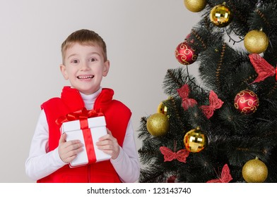 Happy smiling boy with a gifts near the Christmas tree