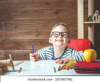Happy smiling boy in glasses. Child with school bag and book. Kid drawing or painting. Child in glasses doing his homework at desk with wooden background. Back to school.