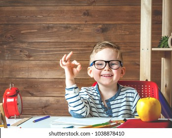 Happy smiling boy in glasses. Child with school bag and book and apple. Kid drawing or painting. Child in glasses doing his homework at desk with wooden background. Back to school.