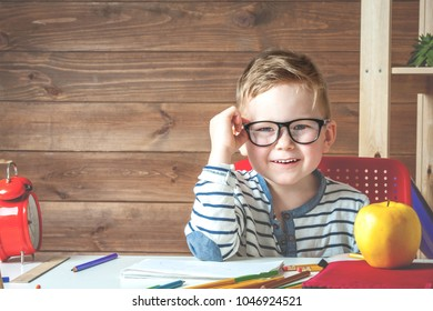 Happy smiling boy in glasses at school for the first time. Child with school bag and book. Kid indoors at home in kid's room interior with wooden background. Back to school. Little boy write to blank
