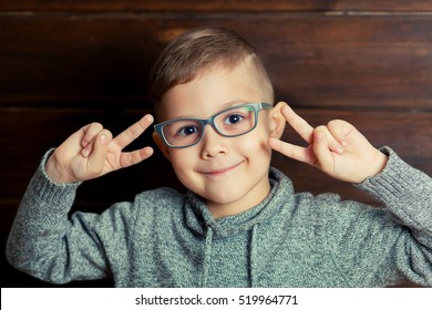 Happy smiling boy in glasses showing peace sign or victory hand triumph on wooden background. Child likes the glasses.