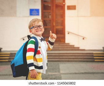 Happy smiling boy in glasses with thumb up is going to school for the first time. Child with bag go to elementary school. Child of primary school. Pupil go study with backpack. Back to school
