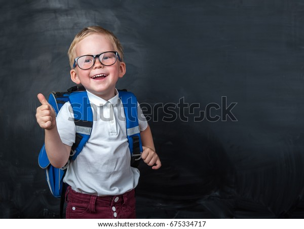 Happy smiling boy in glasses with thumb up is going to school for the first time. Child with school bag and book. Kid indoors of the class room with blackboard on a background. Back to school.