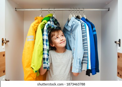 Happy smiling boy searching for clothing in a closet. Preteen boy chooses clothes in the wardrobe closet at home. Kid hiding among clothes in wardrobe.
