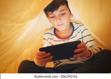 Happy smiling boy sits in bed under a blanket and plays on a smartphone in a game in the dark. The child's face is illuminated by a bright monitor
