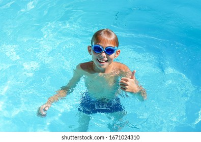 happy smiling boy swimming having fun in the pool. sunny summer day. summer vacation concept
