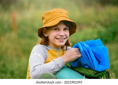 Happy smiling boy tourist opening raincoat because of weather change during trip