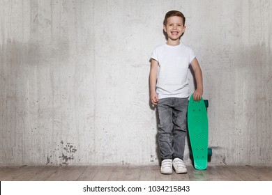 Happy smiling boy in white T-shirt with green skateboard standing in front of gray wall. Concept of sportive life and activity. Skater boy posing, concrete wall on background, copy space.