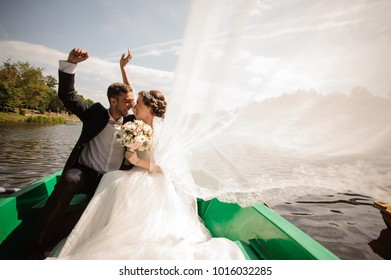 Happy and smiling bride with bridegroom sitting in the boat floating down the river on the sunny day