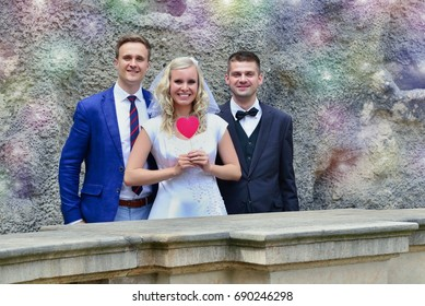 Happy smiling bride holding heart on stick standing midway between two grooms