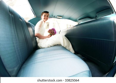 Happy smiling bride in a luxury blue interior car with a bouquet of flowers on her wedding day