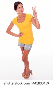 Happy smiling brunette woman gesturing a peace sign while looking at camera and wearing a yellow t-shirt and short jeans isolated