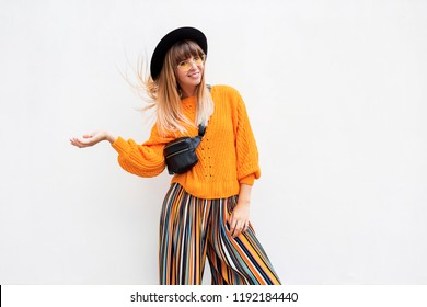 Happy smiling brunette  woman  standing on white background in stylish orange sweater and multicolor stripe culotte , oversize orange knitted sweater, trendy bum bag and hat.