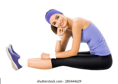 Happy smiling brunette woman in violet sportswear doing fitness stretching exercise or youga moves, isolated on white background. Dark-haired model at studio shot.