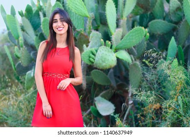 a47498d783 Happy smiling brunette young woman standing in cacti park wearing fashioned  red dress.Stylish trendy