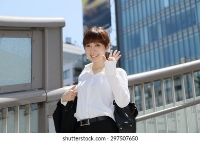 Happy smiling business lady gives a wave