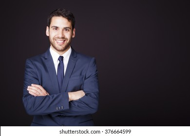 Happy smiling business man with crossed arms on black background