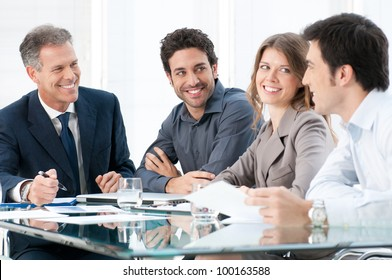Happy smiling business people discussing and working together at office