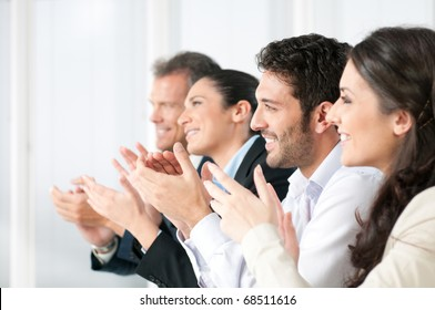 Happy smiling business team clapping hands during a meeting in office