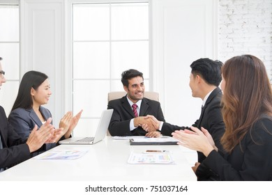 Happy smiling business team clapping hands during a meeting in in a modern office