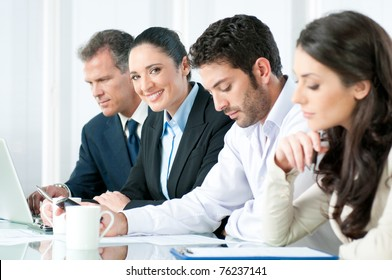 Happy smiling business woman looking at camera while working with colleagues in modern office