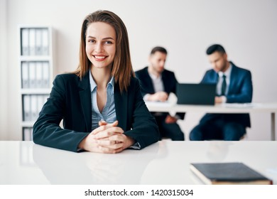 Happy smiling business woman portrait sitting in office with her business team on background. Leadership and success concept