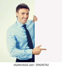 Happy smiling businessman in blue confident business wear, pointing on blank signboard, with copyspace area for slogan or text message