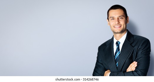 Happy smiling businessman with crossed arms pose, posing at studio, against grey background, with copyspace area for slogan or text message