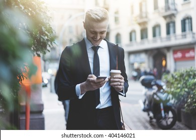Happy smiling businessman going to the work with coffee cup and using modern smartphone outdoors, successful employer using cellphone while on break outside at sunny day near his office
